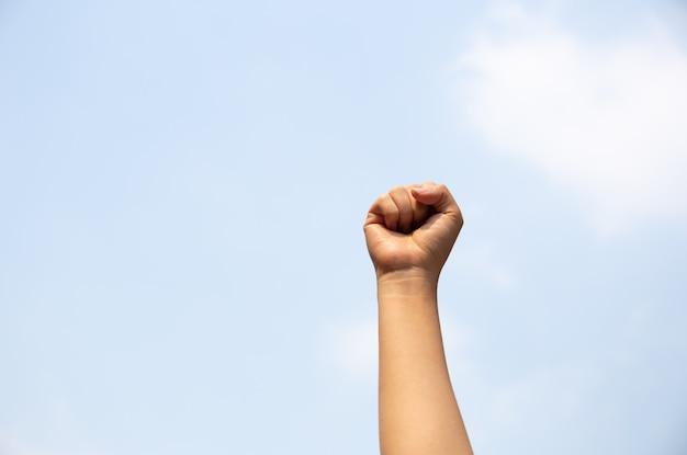 Vrouwenwapen met vuist in de lucht wordt opgeheven die.