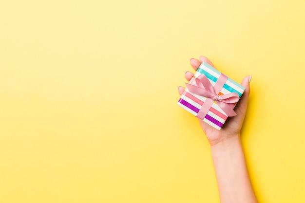 Vrouwenwapens die giftvakje met gekleurd lint op gele lijst houden