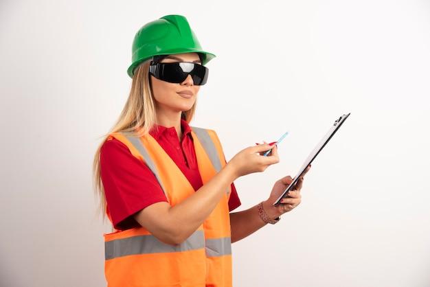 Vrouwenwerknemer die met potlood op klembord tonen.