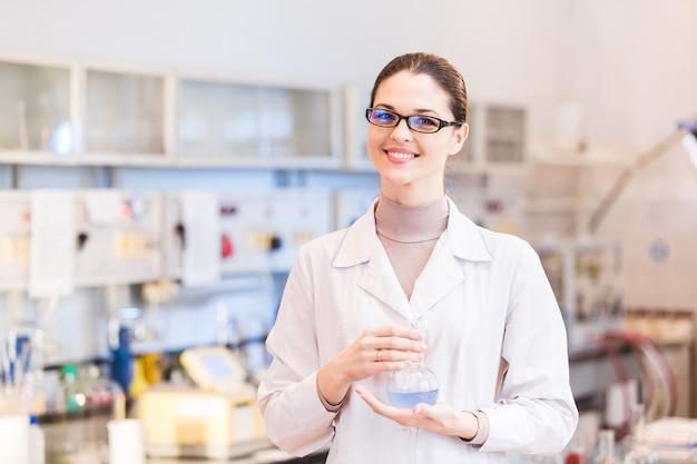 Vrouwenwetenschapper in laboratorium met beker het stellen