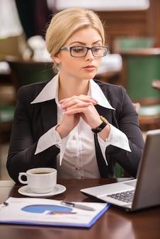 Vrouwenzitting bij de lijst in koffie en het gebruiken van laptop.
