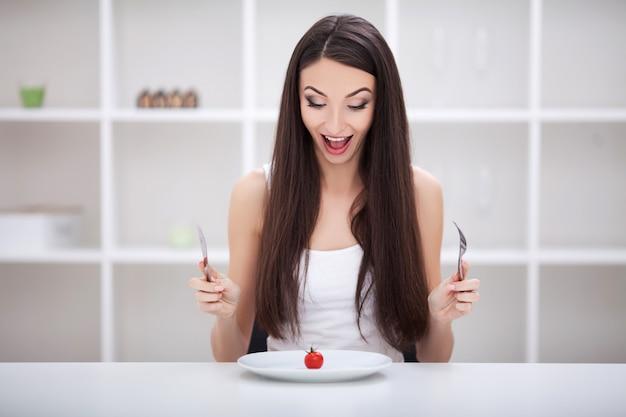 Vrouwenzitting bij een lijst met groenten op een plaat