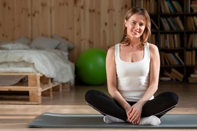 Vrouwenzitting bij yogamat het stellen
