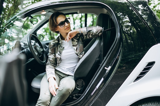 Vrouwenzitting binnen een auto in het bos