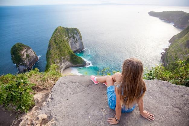 Vrouwenzitting dicht bij de rand en kijkend naar de groene rotsen in de vorm van dinosaurushoofd