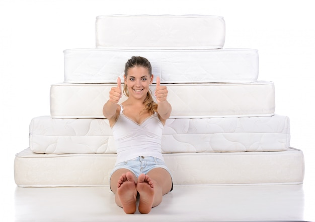 Vrouwenzitting dichtbij vele matrassen.