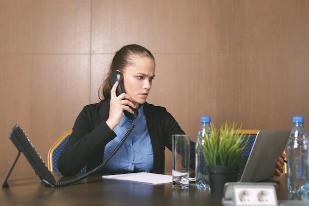 Vrouwenzitting door de lijst met laptop in bureau
