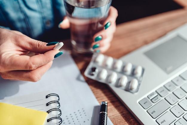 Vrouwenzitting door het bureau en het nemen van medische pillen
