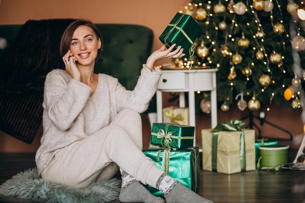 Vrouwenzitting door kerstboom en het winkelen op de telefoon