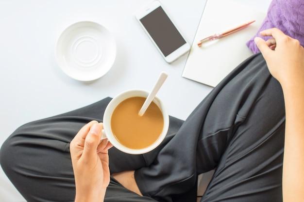 Vrouwenzitting en het drinken koffie met slimme telefoon en notitieboekje op witte vloer. bovenaanzicht.