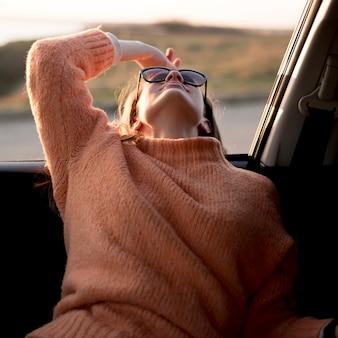 Vrouwenzitting in de auto en het dragen van zonnebril