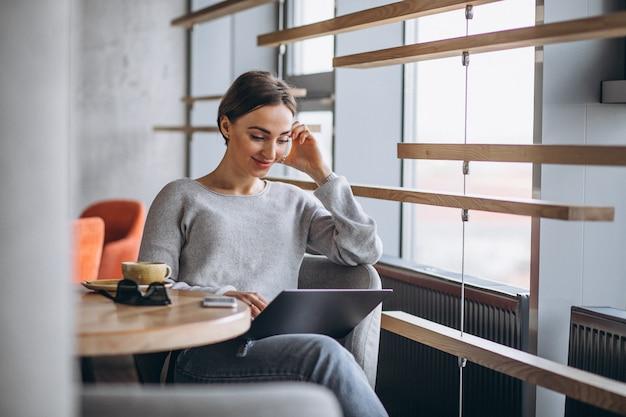Vrouwenzitting in een koffie het drinken koffie en het werken aan een computer