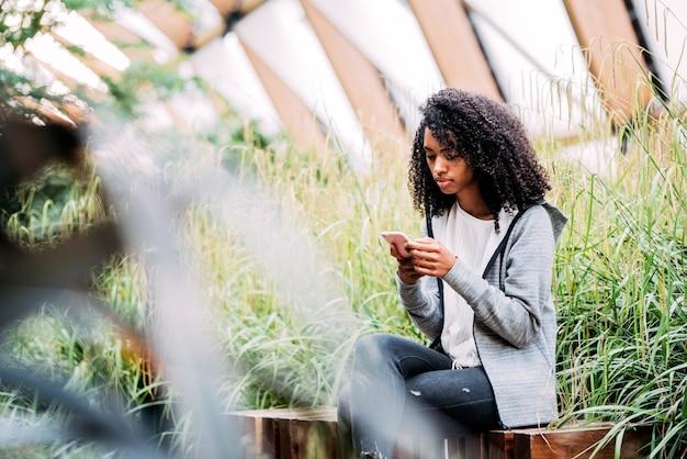 Vrouwenzitting in een mooie tuin die mobiele telefoon met behulp van