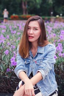 Vrouwenzitting in een park waar de bloemen prachtig bloeien.