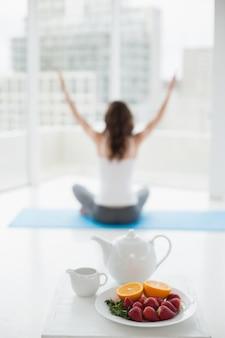 Vrouwenzitting in meditatiehouding met gezond voedsel in voorgrond