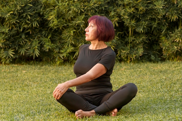 Vrouwenzitting in yogapositie en het doen van rugoefeningen