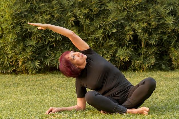 Vrouwenzitting in yogapositie en het uitrekken zich