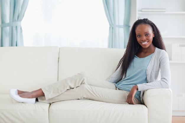 Vrouwenzitting met benen op haar bank