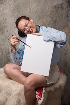 Vrouwenzitting met canvas en penseel op marmeren achtergrond.