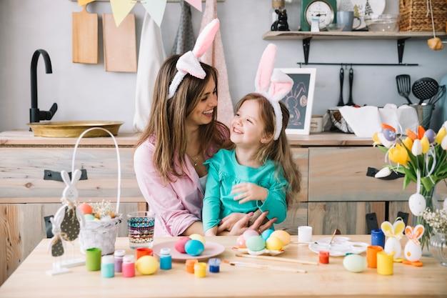 Vrouwenzitting met dochter in konijntjesoren dichtbij paaseieren