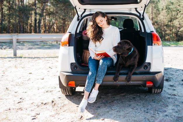 Vrouwenzitting met haar hond in open boomstam