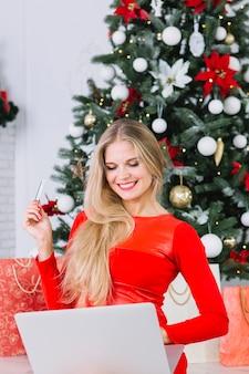 Vrouwenzitting met laptop dichtbij kerstboom