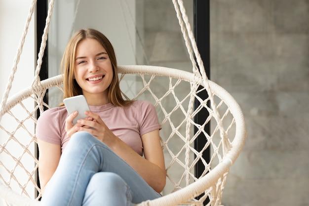 Vrouwenzitting naast een venster terwijl het houden van haar telefoon