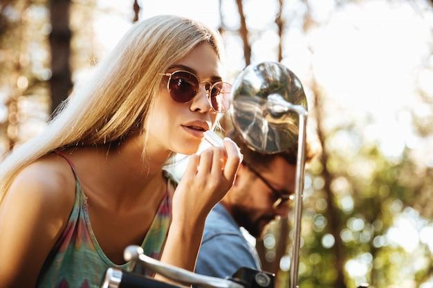 Vrouwenzitting op autoped die in openlucht make-up van lippen doen.