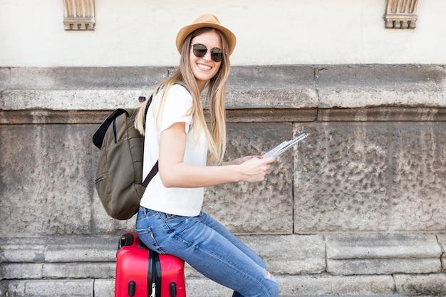 Vrouwenzitting op bagageglimlachen bij camera