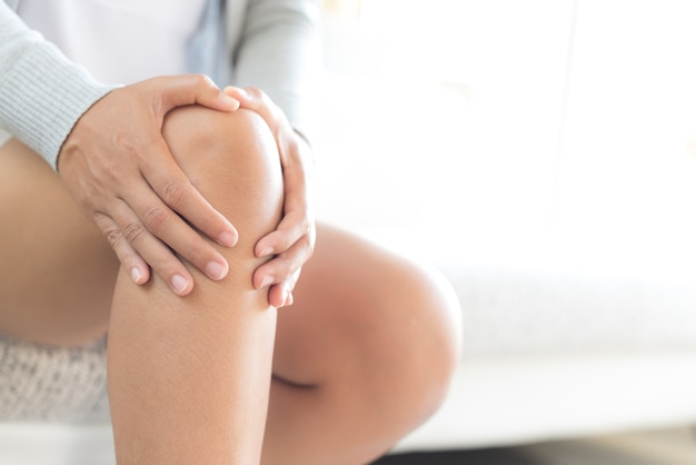 Vrouwenzitting op bank en het voelen van kniepijn. gezondheidszorg en medisch concept.