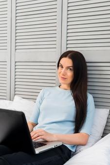 Vrouwenzitting op bed met laptop