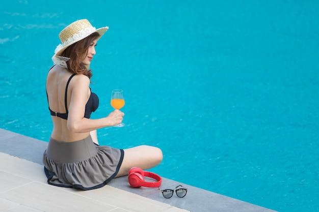 Vrouwenzitting op bed naast zwembad