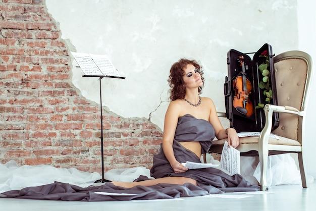 Vrouwenzitting op de vloer dichtbij de stoel met viool