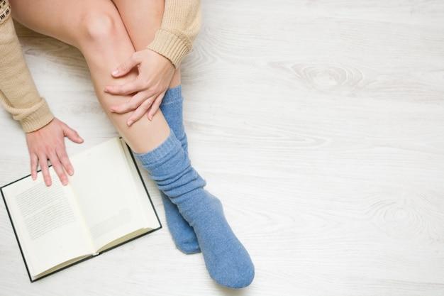 Vrouwenzitting op de vloer die een het boek hoogste mening en exemplaarruimte lezen