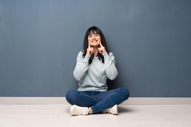 Vrouwenzitting op de vloer die met een gelukkige en prettige uitdrukking glimlachen