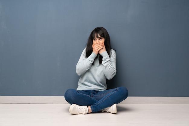 Vrouwenzitting op de vloer die mond behandelt en aan de kant kijkt