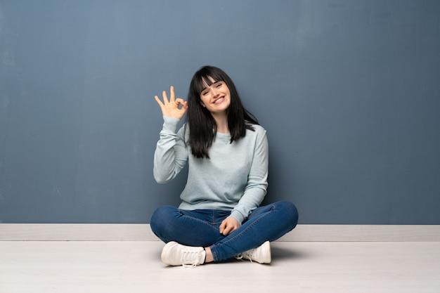 Vrouwenzitting op de vloer die ok teken met vingers tonen