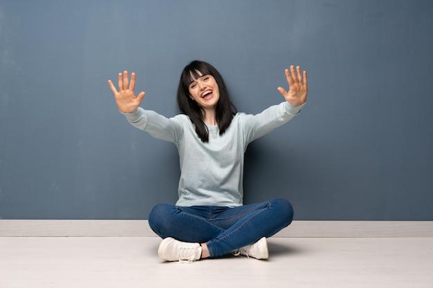 Vrouwenzitting op de vloer die tien met vingers tellen