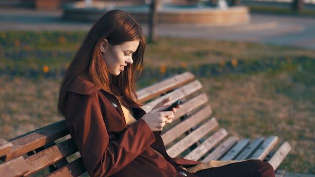 Vrouwenzitting op een bank in een park, de herfst