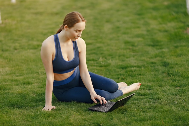 Vrouwenzitting op een gras en gebruikt laptop