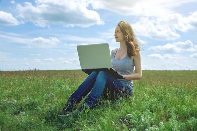 Vrouwenzitting op een groene weide, hemel met wolken en het werken of het bestuderen met draadloze laptop