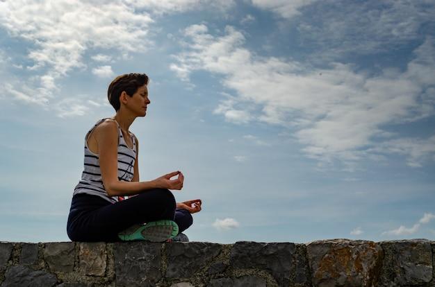 Vrouwenzitting op een muur, die yoga doet.