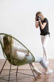 Vrouwenzitting op een stoel en een fotograaf lang schot