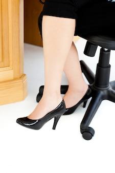 Vrouwenzitting op een stoel met haar voeten op de vloer