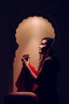 Vrouwenzitting op een verfraaid marokkaans venster bij een hoteltoevlucht die traditionele thee drinken