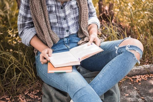 Vrouwenzitting op gazon en het houden van geopend boek