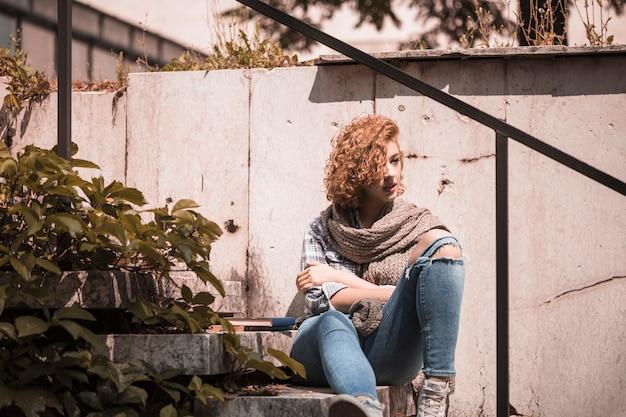 Vrouwenzitting op stappen dichtbij boeken in openbare tuin