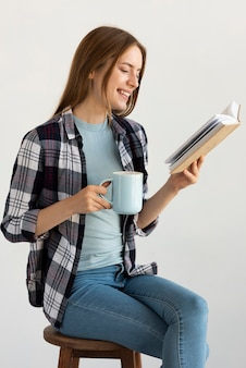 Vrouwenzitting op stoel terwijl het lezen van een boek
