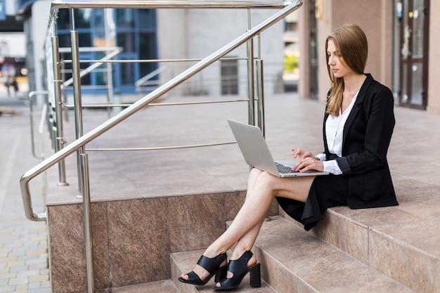 Vrouwenzitting op treden die haar laptop met behulp van