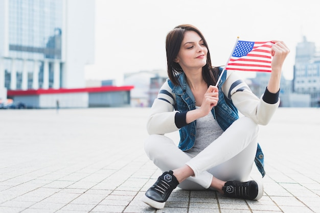 Vrouwenzitting op vierkant en amerikaanse vlag in hand houden